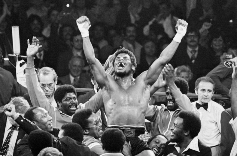 Leon Spinks celebrates in the ring after beating Muhammad Ali.