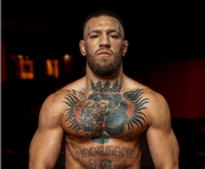 Conor McGregor has a stern look on his face and boasts ample tattoo ink on his body.